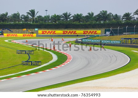 SEPANG, MALAYSIA - APRIL 9: Marshals clean track for qualification of Formula 1 GP, April 9 2011, Sepang, Malaysia - stock photo
