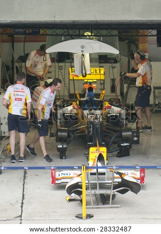 SEPANG, MALAYSIA- APRIL 3: Mechanics prepare Nelson Piquet Jr.'s car of ING Renault F1 Team during practice session at Malaysian F1 Grand Prix April 3, 2009 at Sepang International Circuit in Sepang. - stock photo