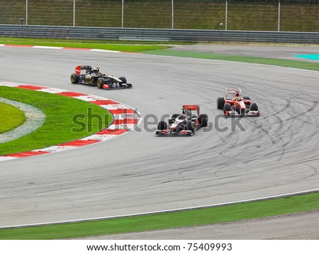 SEPANG, MALAYSIA - APRIL 10: Unidentified racers round one of the curves on the track at the Formula 1 GP race on  April 10 2011 in  Sepang, Malaysia - stock photo