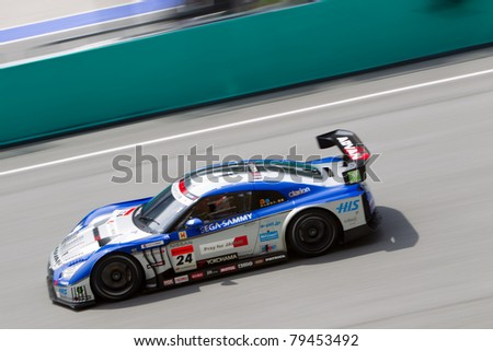 SEPANG, MALAYSIA - JUNE 18: Team Kondo Racing in their Nissan GTR goes past the pit lane during qualifying at Super GT International series June 18, 2011 in Sepang, Malaysia - stock photo