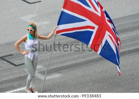 SEPANG, MALAYSIA - MARCH 25 : Grid girl holds British flag during the opening ceremony of F1 Petronas Malaysian Grand Prix at Sepang F1 circuit on March 25, 2012 in Sepang, Malaysia - stock photo