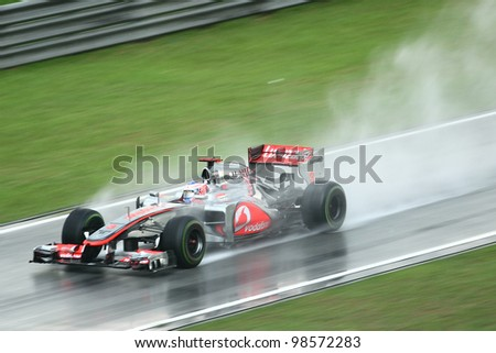 SEPANG,MALAYSIA - MARCH 25: Jenson Button of Vodafone McLaren Mercedes team in action during rain-hit Formula One PETRONAS Malaysian Grand Prix at Sepang F1 Circuit on 25 March,2012 in Sepang,Malaysia - stock photo