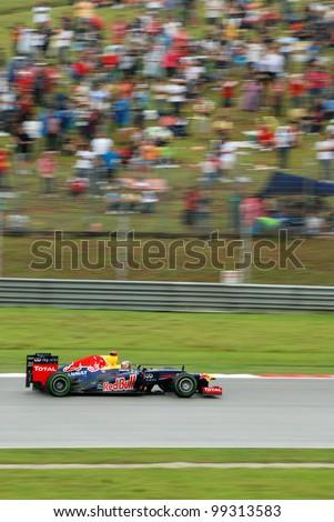SEPANG, MALAYSIA-MARCH 25 : Red Bull F1 driver Sebastian Vettel pass through the spectators during race day of Petronas F1 Malaysian Grand Prix at Sepang Circuit on March 25, 2012 in Sepang, Malaysia - stock photo