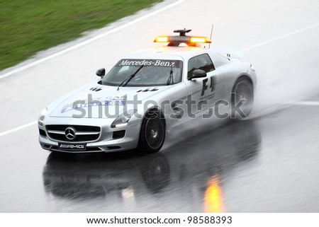 SEPANG, MALAYSIA - MARCH 25: Safety car lead the Formula One racer during heavy rain downpour in Formula One PETRONAS Malaysian Grand Prix at Sepang F1 circuit on 25 March, 2012 in Sepang, Malaysia - stock photo