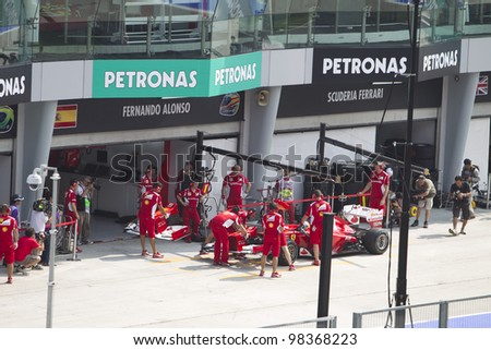 SEPANG, MALAYSIA - MARCH 23: Spanish Fernando Alonso of Team Scuderia Ferrari changes his front nose wing during Friday practice at Petronas Formula 1 Grand Prix March 23, 2012 in Sepang, Malaysia - stock photo