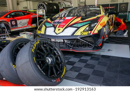 SEPANG, MALAYSIA - MAY 11, 2014: Unidentified team mechanics work on the cars for the Lamborghini Super Trofeo race, part of the Malaysian Super Series Rd 2 held at the Sepang International Circuit. - stock photo