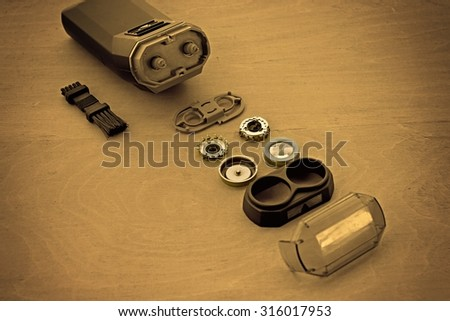 Separate elements of electric shaver on wooden table. - stock photo