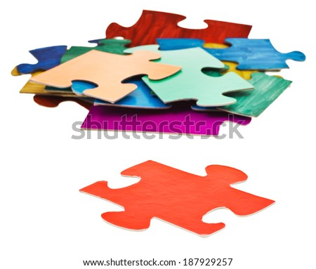separate red puzzle piece in front of pile of jigsaw puzzles isolated on white background - stock photo