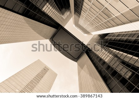 Sepia abstract buildings made of steel and glass. High urban impressive modern construction concept. Monochrome business center view over dramatic sky. Finance center sepia conceptual background.  - stock photo