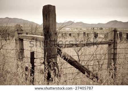 Sepia country fencepost looking over a valley in southern Arizona - stock photo
