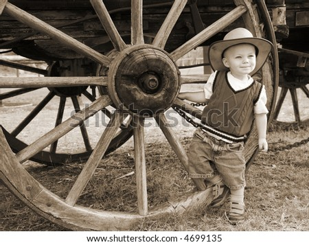 Sepia Farmboy:  A baby cowboy hangs out at the wheel of an old farm wagon in a cowboy hat and denim shorts. - stock photo