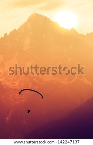 Sepia paraglide silhouette over Alps peaks - stock photo