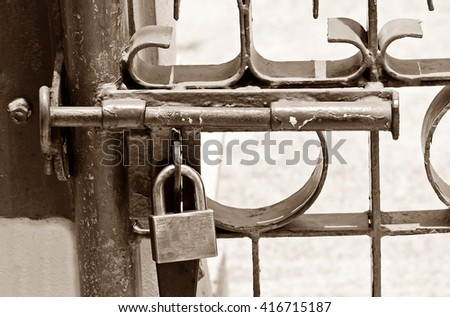sepia tone of aged fence door locked by bolt and padlock - stock photo