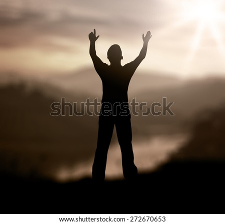 Sepia tone. Silhouette of man with hands raised to beautiful sunset background. - stock photo