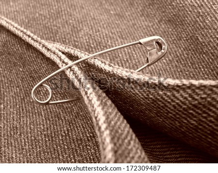 sepia toned clothing fragment with safety pin                                - stock photo