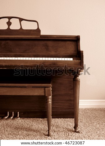 Sepia toned piano in living room of house against wall - stock photo
