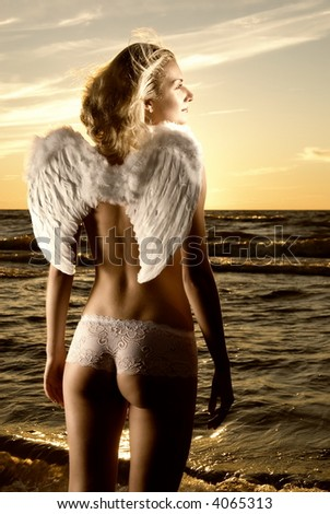 Sepia toned picture of a beautiful angel in a sea at sunset time - stock photo