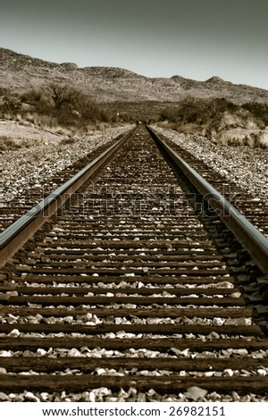 Sepia train tracks leading in to the desert horizon - stock photo
