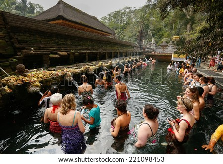 SEPTEMBER 18, 2014 - BALI, INDONESIA: Devotees bathe in the temple pool of Pura Tirta Empul in a cleansing and purification ceremony. Hinduism is the religion of the Balinese people. - stock photo