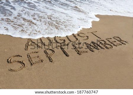 September is coming concept - inscription August and September written on a sandy beach, the wave is starting to cover the word August.  - stock photo