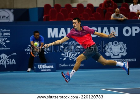 SEPTEMBER 23, 2014 - KUALA LUMPUR, MALAYSIA: Bernard Tomic of Australia makes a forehand return in his first round match at the Malaysian Open Tennis 2014 event. This is an ATP sanctioned tournament. - stock photo