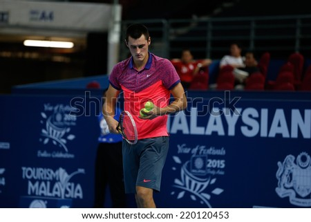 SEPTEMBER 23, 2014 - KUALA LUMPUR, MALAYSIA: Bernard Tomic of Australia prepares to make a serve in his first round match at the Malaysian Open Tennis 2014 event. This is an ATP sanctioned tournament. - stock photo