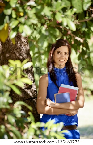 Sequence of students portrait at school, happy young woman smiling with college textbooks in park leaning on tree - stock photo