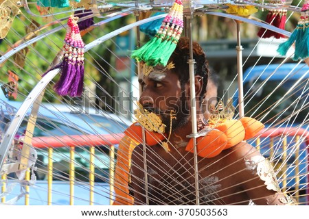 Serangoon, Singapore - 24 Jan 2016: A Hindu devotee carrying a kavadi in the annual Thaipusam festival procession, celebrated mainly by Tamil Indians - stock photo