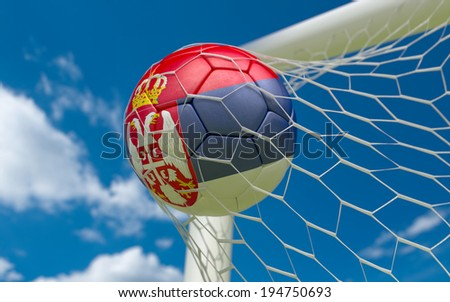 Serbia flag and soccer ball, football in goal net - stock photo