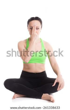 Serene beautiful girl practicing yoga nadi shodhana pranayama (Alternate Nostril Breathing), sitting in Easy Pose, Sukhasana, meditation, hands in smiling Buddha mudra - stock photo