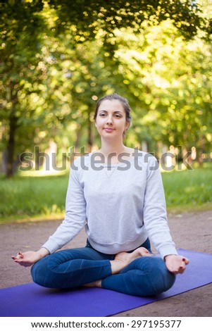 Serene beautiful sporty young woman sitting cross legged in Ardha Padmasana, half lotus posture on blue mat on the street in park alley, asana for meditation, breathing exercises, vertical shot - stock photo