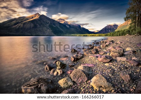 Serene Lake McDonald in Glacier National Park, MT surrounded by mountains and a pine forest, long exposure - stock photo