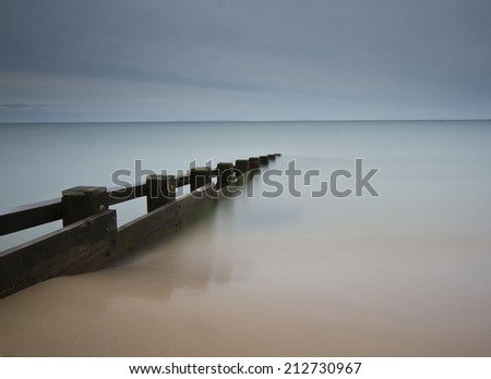 Serene long exposure of groyne going out to sea from sand - stock photo