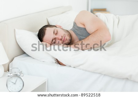 Serene man sleeping in his bedroom - stock photo