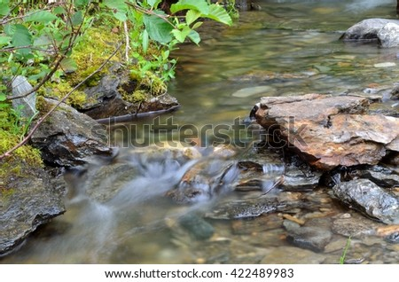 serene mountain creek flow in summer nature - stock photo
