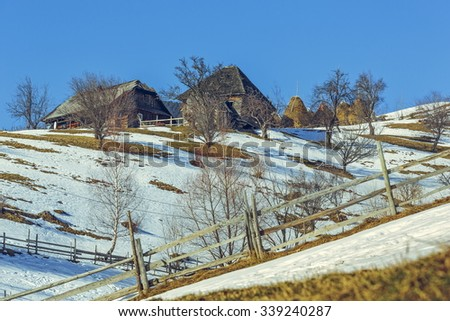 Serene rural landscape with old traditional Romanian wooden houses and melting snow during spring uphill in Magura village, Transylvania region, Romania. - stock photo