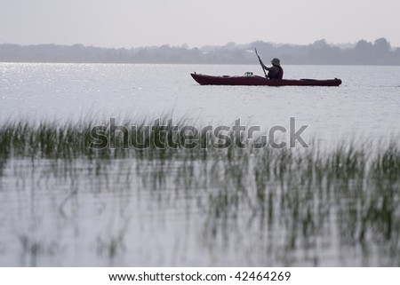 Serene scene of woman kayaking. - stock photo