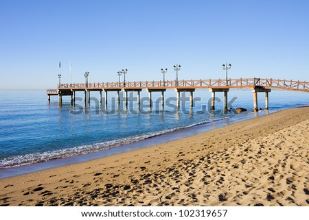 Serene scenery of a sandy beach and a wooden pier on Costa del Sol between resort town of Marbella and Puerto Banus in Spain, Malaga province - stock photo