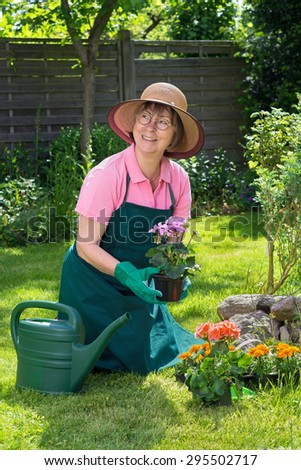 Serene smiling middle aged woman wearing glasses, beige sunhat, pink polo shirt, green overalls and green gardening gloves kneels beside watering can on grass in gardening holding plant in flower pot - stock photo