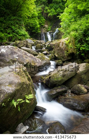 Serene waterfall in a rocky green rain forest, Ring of Kerry, Ireland - stock photo