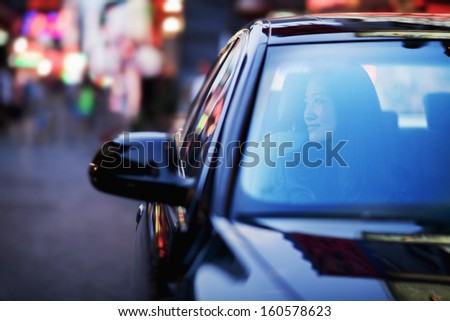 Serene woman looking through car window at city nightlife - stock photo