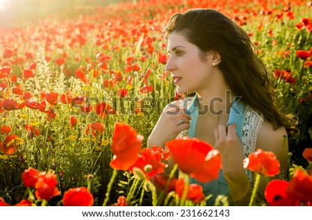 Serene woman posing in colorful poppies field - stock photo
