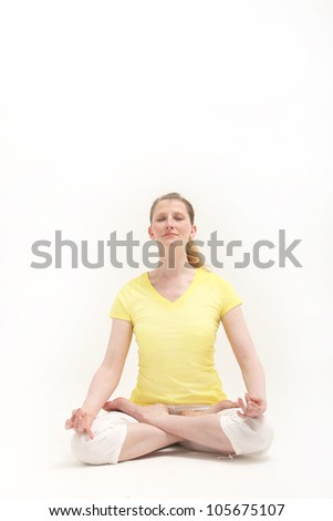 Serene woman sitting on the floor in the lotus position meditating while practising yoga - stock photo