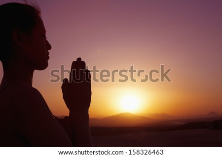 Serene young woman with hands together in prayer pose - stock photo