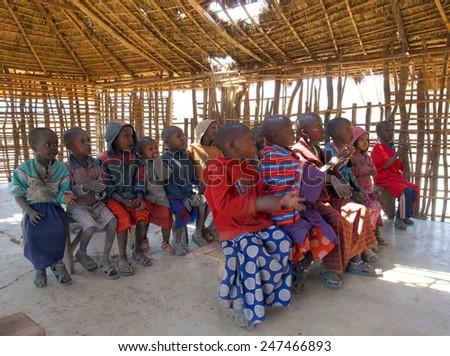 SERENGETI ,TANZANIA - JUNE 20 ; Maasai children at there classroom on june 20,2013 .Tanzania.Only 48 percent of Maasai children  go to school, only 10 percent of them make it to secondary school.  - stock photo