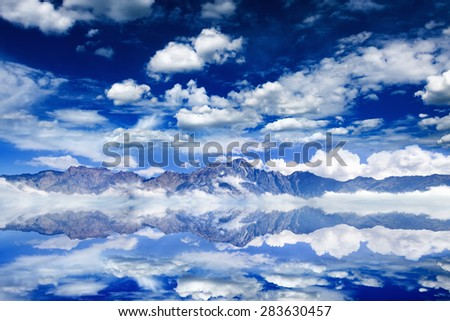 Serenity nature background - dark blue sky, white clouds and mountains reflected in water - stock photo