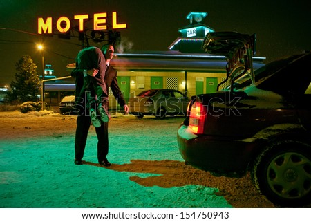 Serial Killer with a corpse on his shoulder ready to put it in the trunk - stock photo