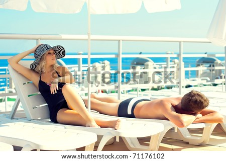 Series man and woman lying on chaise lounges on a yacht in the ocean - stock photo
