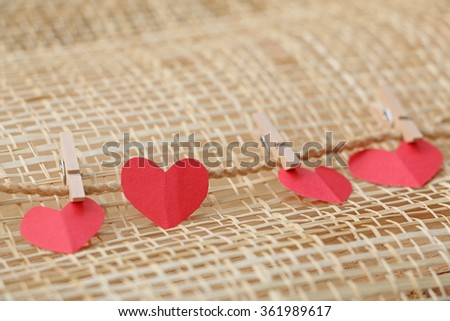 Series of Valentines Card. Four Red heart paper cut with clothes pin on wooden weaving background, in very shallow focus. Image of Valentines day. - stock photo