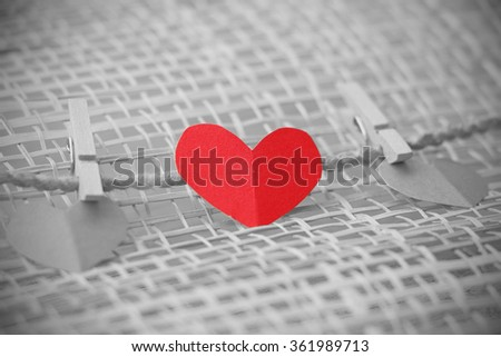 Series of Valentines Card. Three Red heart paper cut with clothes pin on wooden weaving background, in very shallow focus. Image of Valentines day. Selective Color. - stock photo